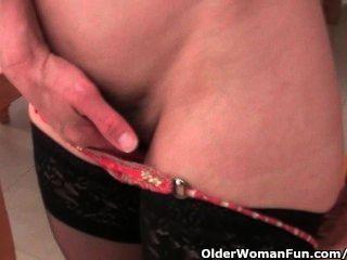 Abuelita en medias trabaja su coño peludo con un consolador
