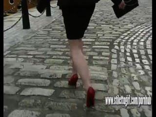 Sexy mujer de tacón alto caminando sobre adoquines llevando delgado estiletes rojos