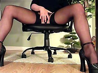 Secretaria bajo vista de escritorio de masturbación en tacones y medias