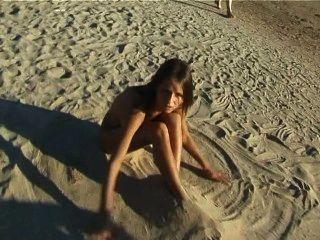 Hermosa jugaba adolescente fresco en la playa desnuda