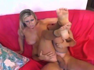Rubia con tetas grandes follando y dando un footjob en nilones crotchless desnudo