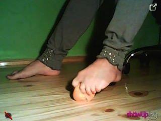 Chica aplastando una mandarina con sus pies