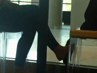 Zapatos candentes y pies en la cafetería