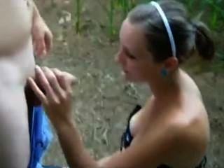 Linda chica blanca da a un chico blanco y negro una mamada en la naturaleza