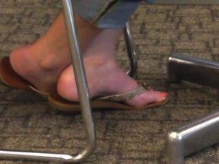 Los pies y los dedos del pie rubios sinceros en chancletas