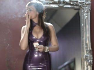Chica fumar cigarrillos fuertes en vestido de látex púrpura