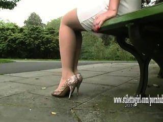 Hermosa niña muestra sus piernas de nylon suave sedoso y elegantes tacones altos