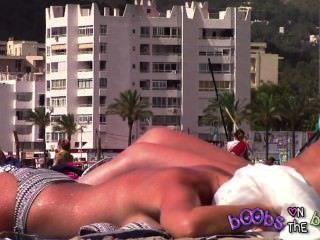 Taninos épicos y un pezón perforado en tetas falsas en la playa con topless
