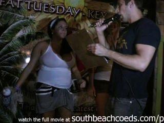 Muchachas universitarias reales calientes que hacen competencia mojada de la camiseta en la playa del sur de la rotura de primavera