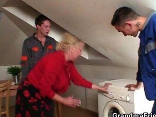 Solitaria abuela separa piernas para dos reparadores