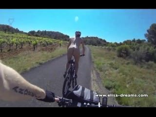 Intermitente y desnudo en público en bicicleta en la carretera