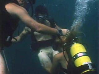 Chica en equipo de buceo hace una mamada para dos buceadores