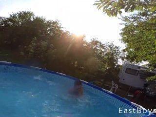Gemelos lindos luchan desnudos en la piscina