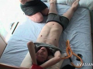Sexy asiática adolescente tomándose un amigo atado