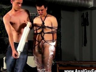 Gay twinks cristian está casi balanceándose, envuelto en cuerda y encadenado